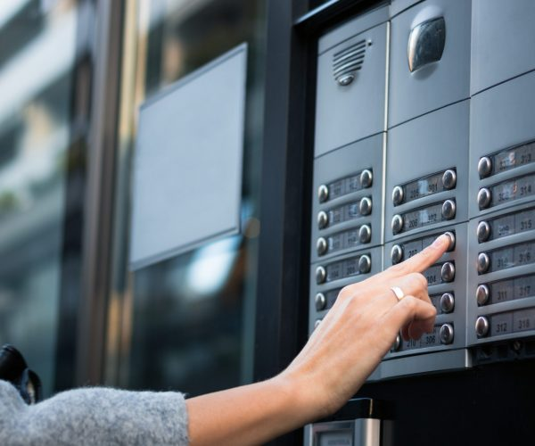 Close up of woman using intercom at residential building entrance.