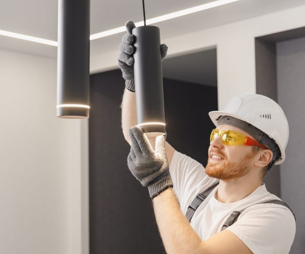 Electrician installs lamp lighting and spot loft style on ceiling.