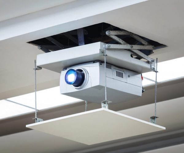 Old and dirty projector hang on ceiling in meeting room, education concept